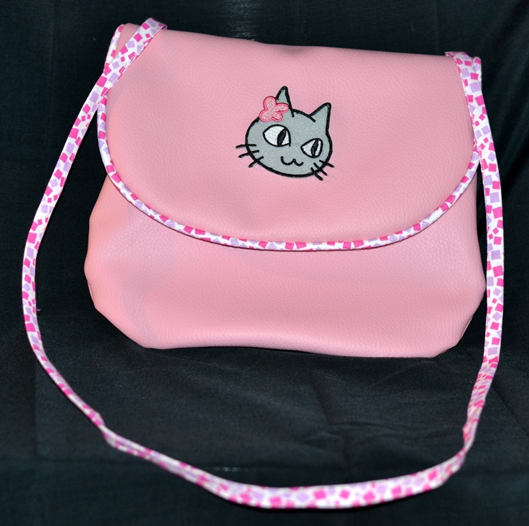 """Pochette demoiselle en détresse, simili cuir rose, rabat bordé d'un passepoil assorti, badge """"Petit chat fille coquette"""" cousu en appliqué"""